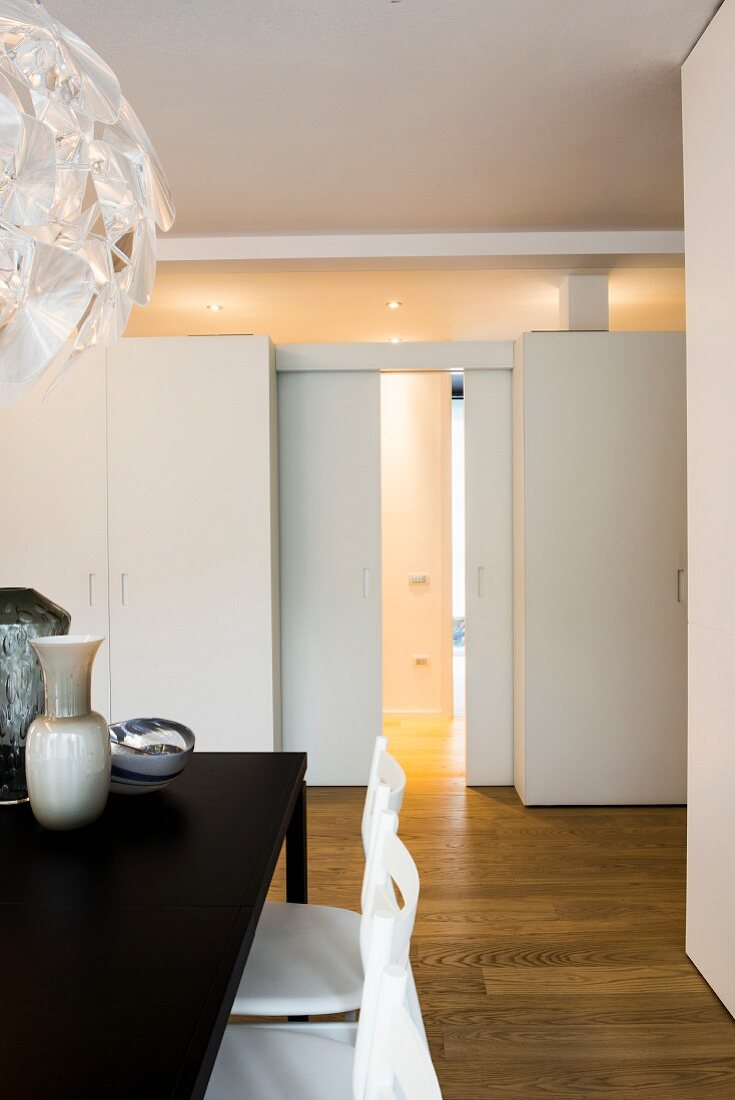 View past dining table to wall with sliding doors, transom window and fitted cupboards