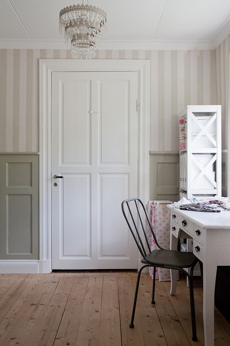 Sewing area in room with panelled walls and striped wallpaper