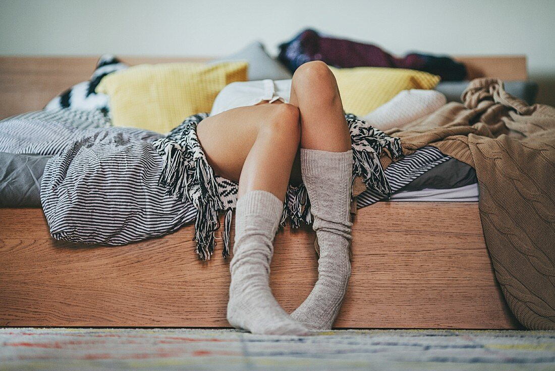 Young woman wearing knee socks lying on bed