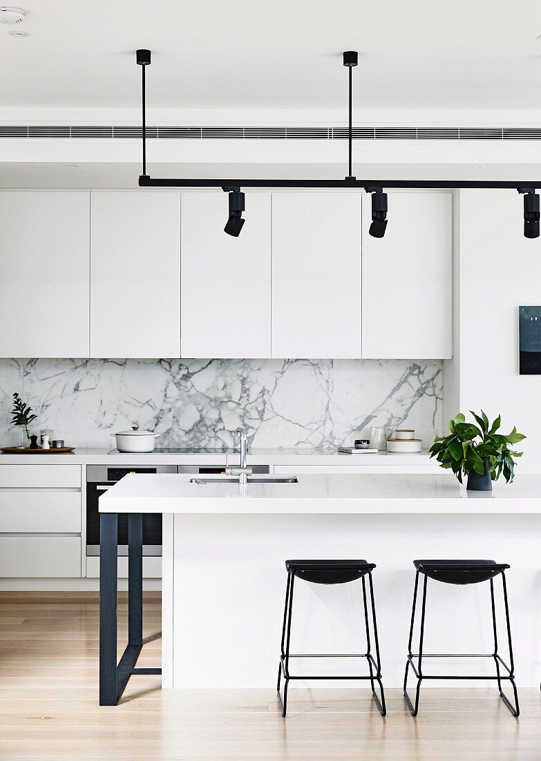 Black bar stools in front of a white kitchen island under a light rail with black spotlights in an open designer kitchen with marble splash protection