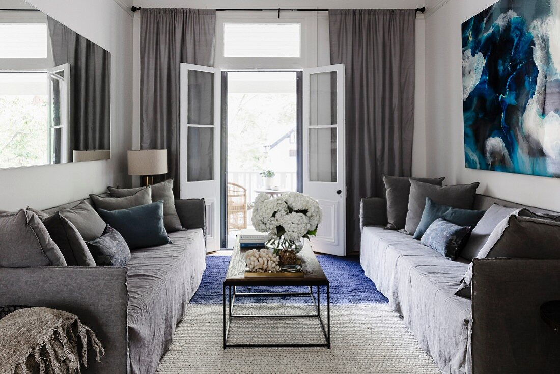 Cozy, gray sofa set and coffee table with metal base in front of an open balcony door