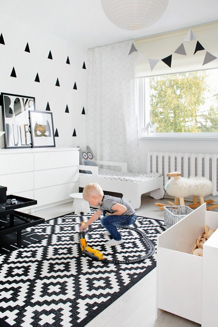 Little boy playing on rug in monochrome child's bedroom