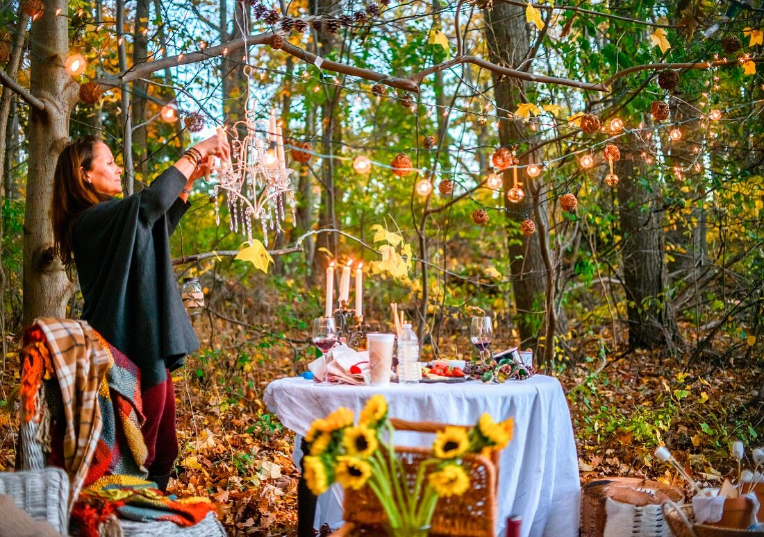 Woman decorating set table in autumnal woodland with fairy lights and crystal chandelier