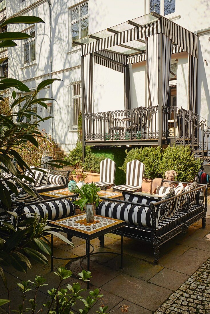 Outdoor furniture on terrace and roofed balcony with pelmets and curtains