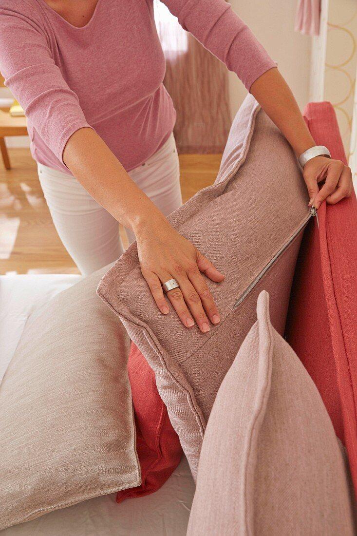 A woman zipping a back cushion to a headboard