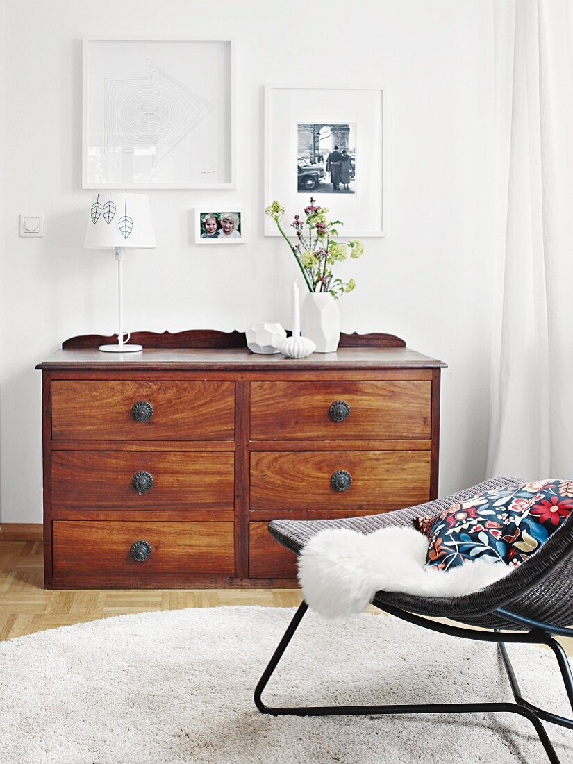Pictures in white frames hung above an antique wooden chest of drawers with a carved back edge
