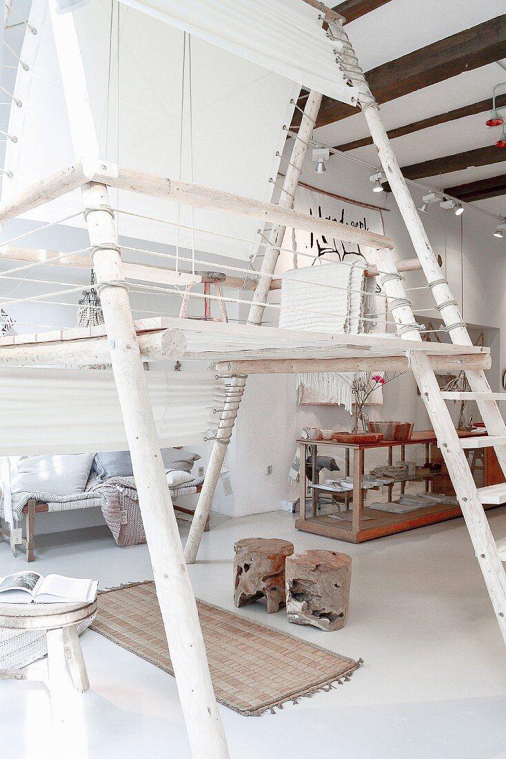 Loftartiger Raum mit freistehender Galerie aus Rundhölzern