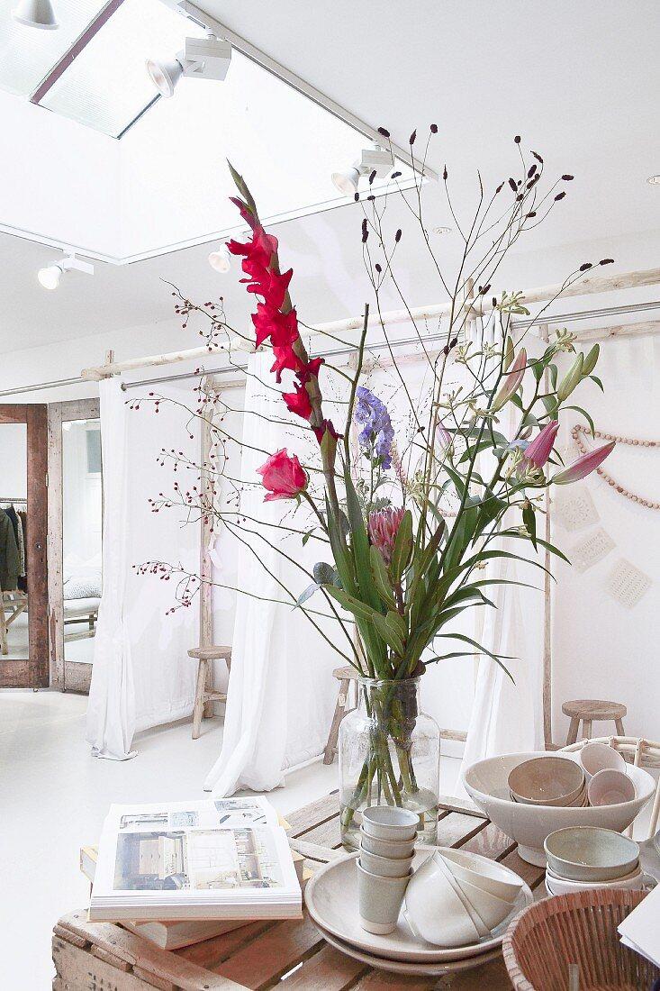 Bunter Blumenstrauss mit Gladiole in Vase und Geschirr auf Tisch