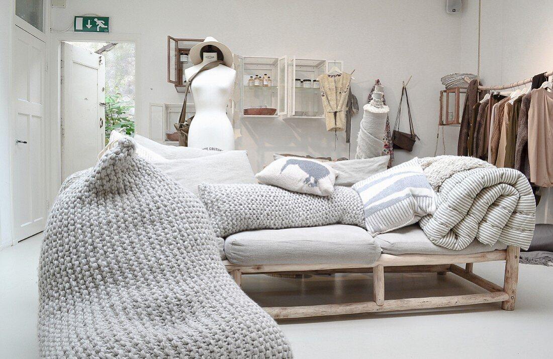 Sofa mit Polstern auf Holzgestell aus Rundhölzern, Kissen mit Häkelbezug im Verkaufsraum