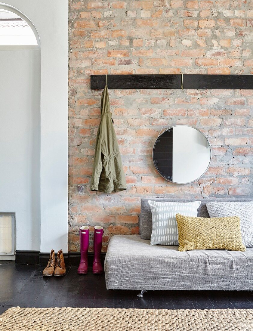 Grey sofa below coat rack and round mirror on brick wall