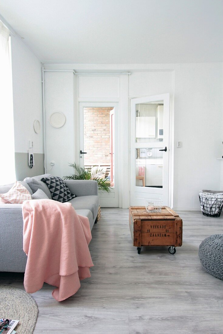 Pink blanket on pale grey couch behind vintage wooden crate used as coffee table