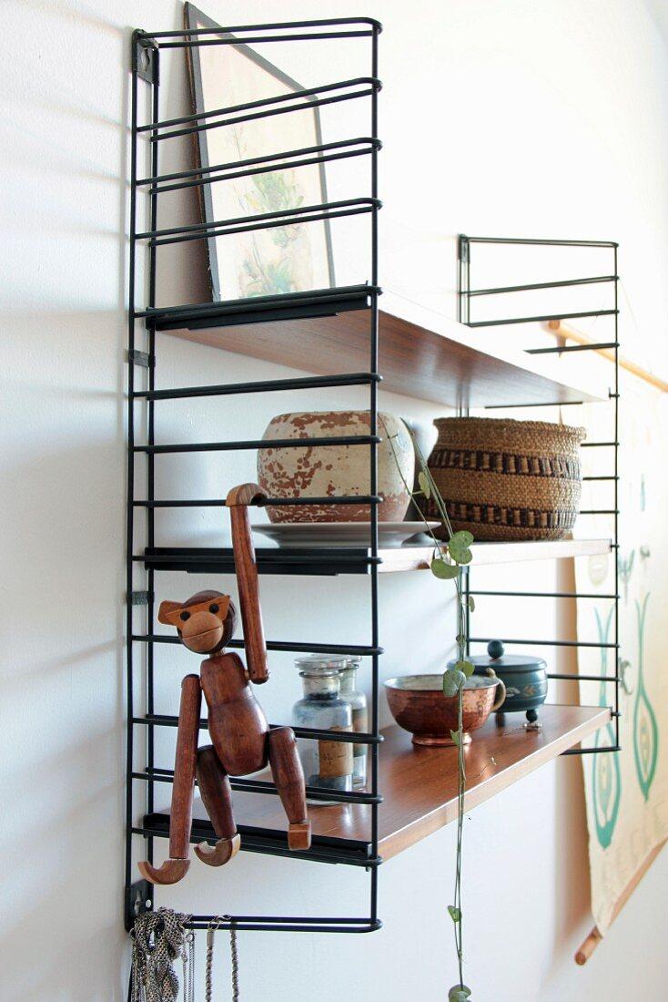 String-Regal mit Affenfigur, Kupfertasse und Vintage Behältern