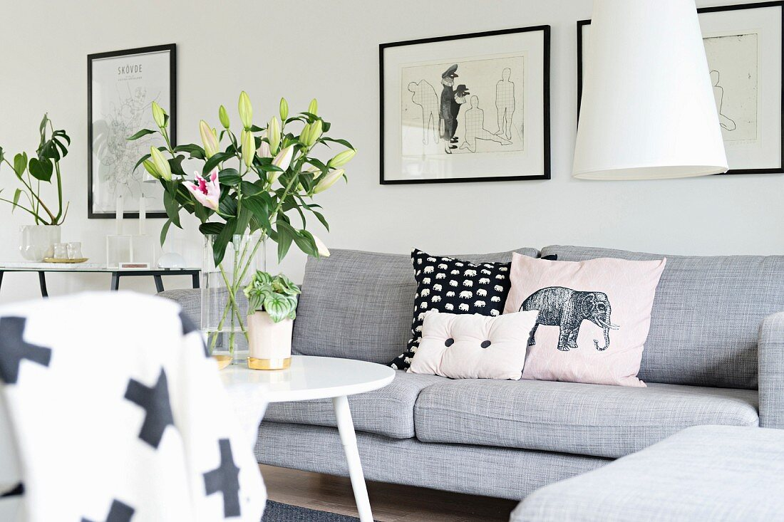Scatter cushions on pale grey couch and vase of lilies on round table
