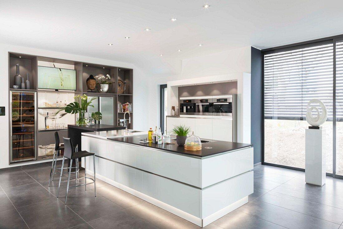 A white kitchen island with base lighting in an open-plan designer kitchen