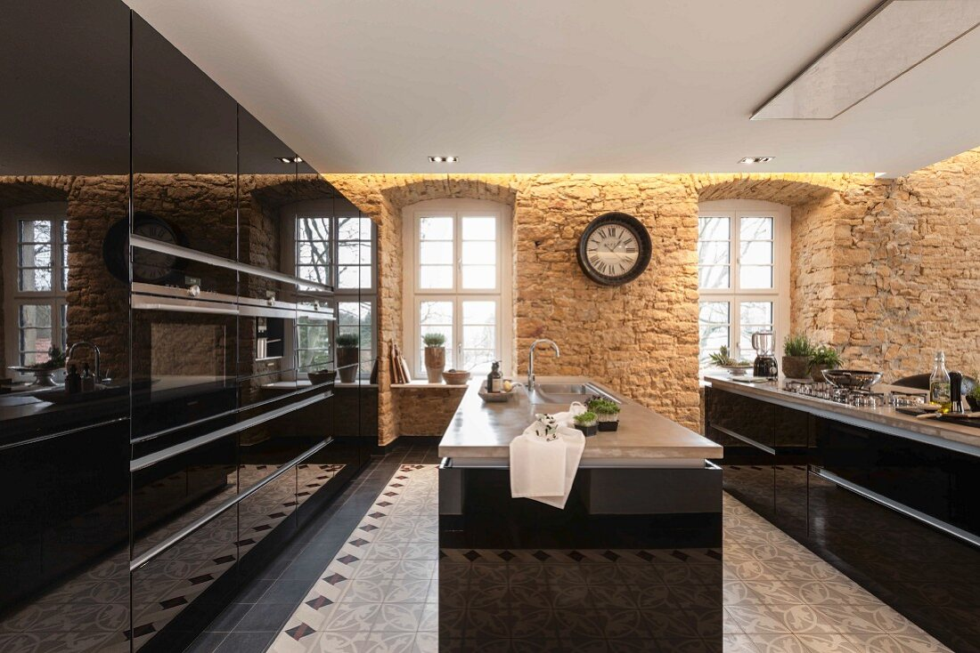 A modern kitchen with shiny, black wooden surfaces and islands with sandstone walls fitted with indirect lighting and a suspended ceiling