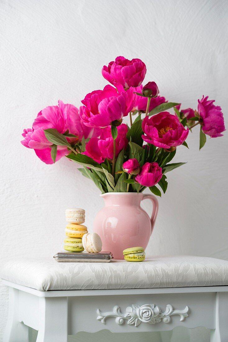 Macarons next to jug of pink peonies on white stool