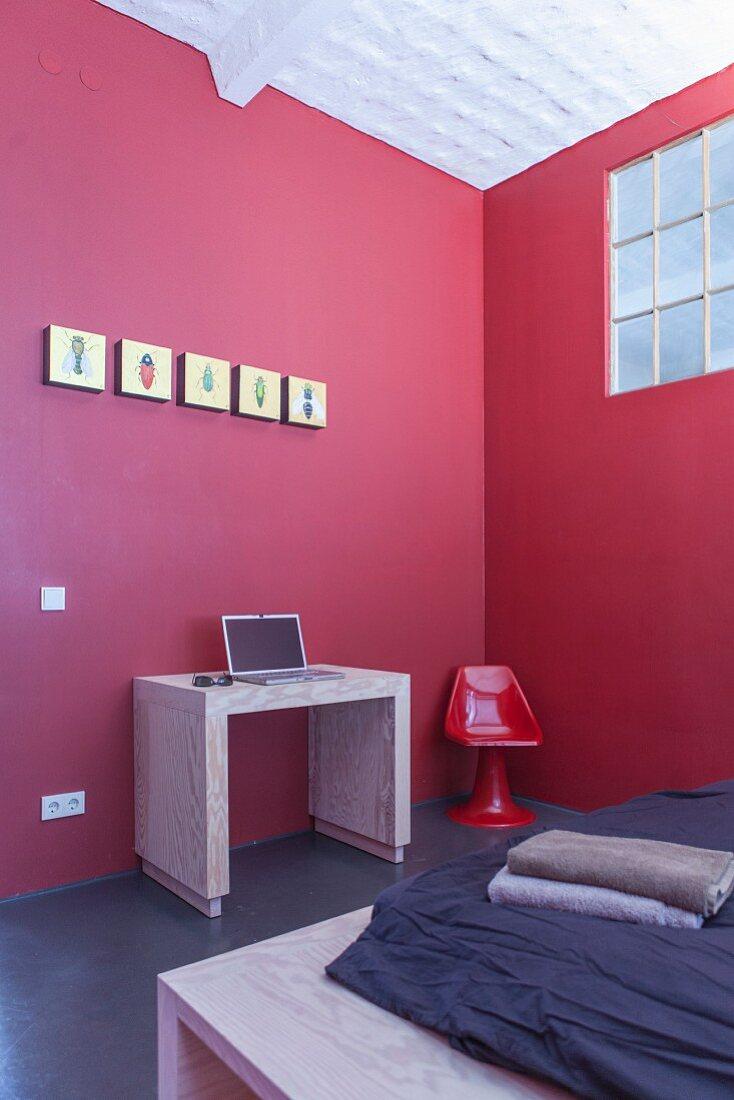 Laptop desk against red wall in minimalist workspace in corner of bedroom with industrial windows