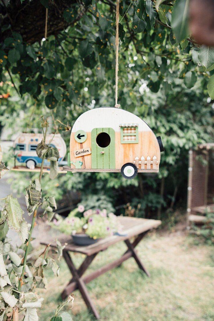 Caravan-shaped bird nesting box hanging in a tree