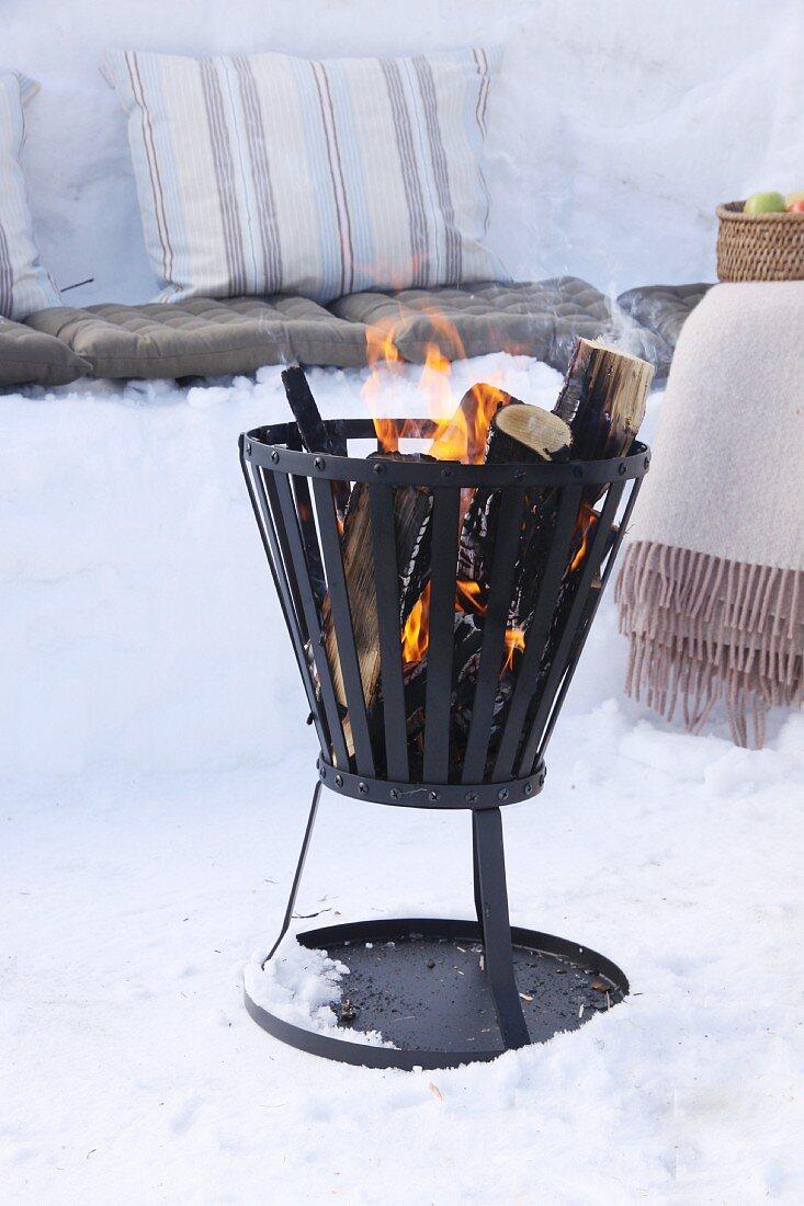 Fire basket amongst snow for winter picnic
