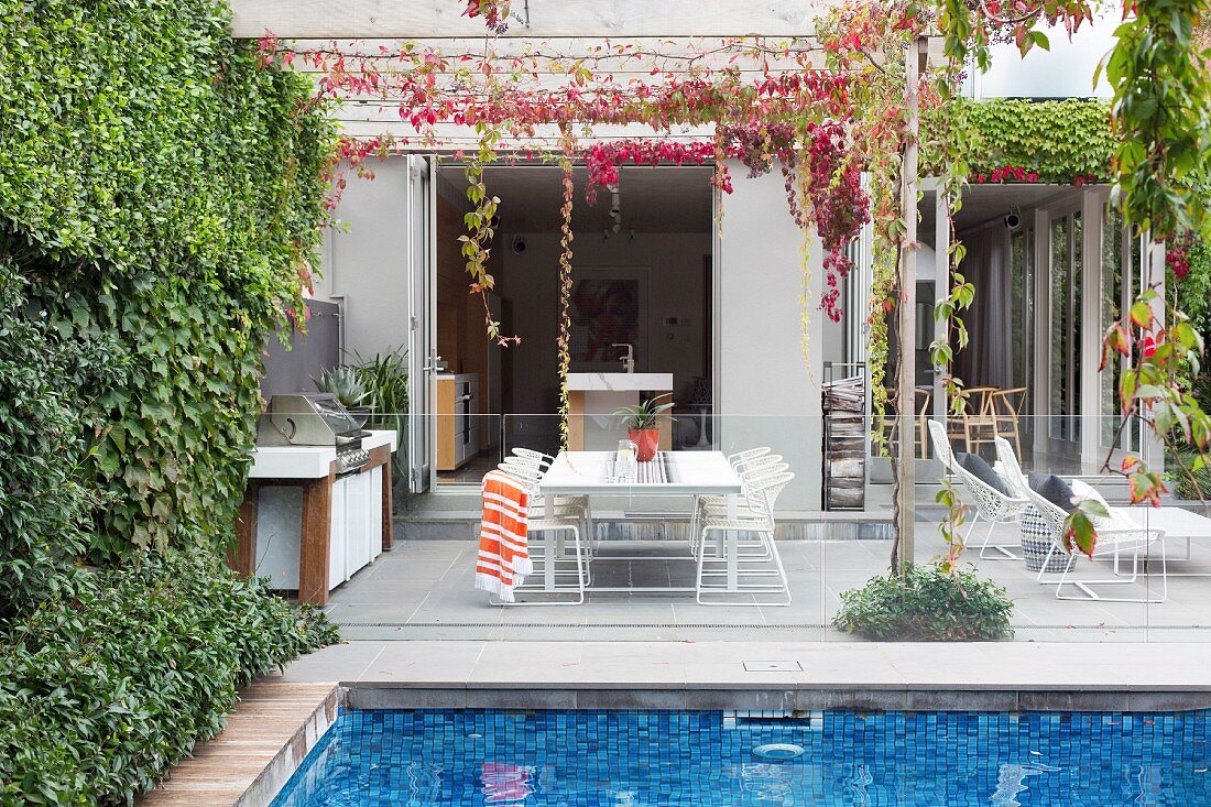 Pool with glass balustrade in front of the terrace with outdoor kitchen and lounge