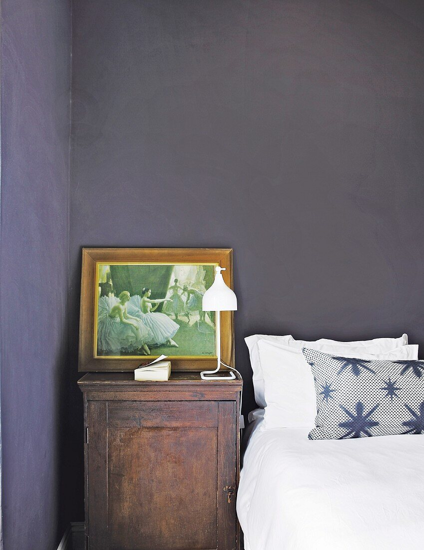 Picture on old bedside cabinet in bedroom with black walls
