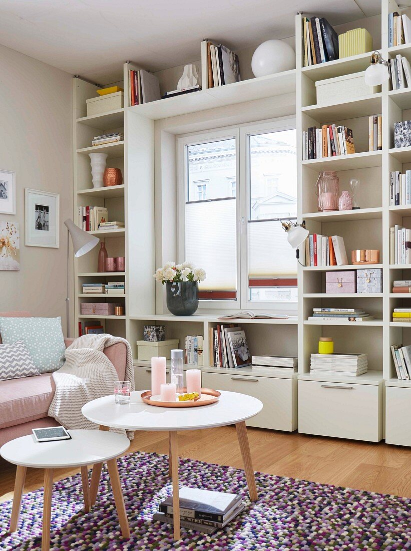 A natural white, made-to-measure shelf built around a window in a feminine room
