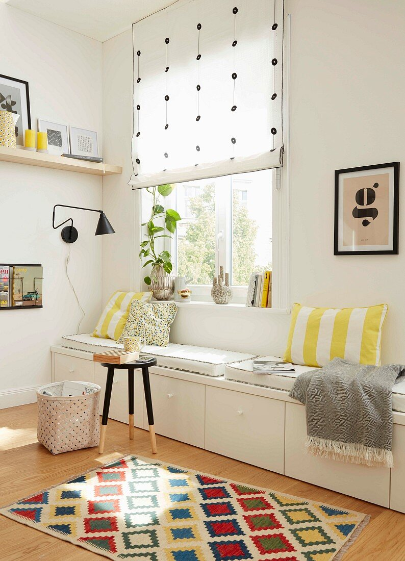 A white, made-to-measure with drawers and cushions in a light corner of a room under a window