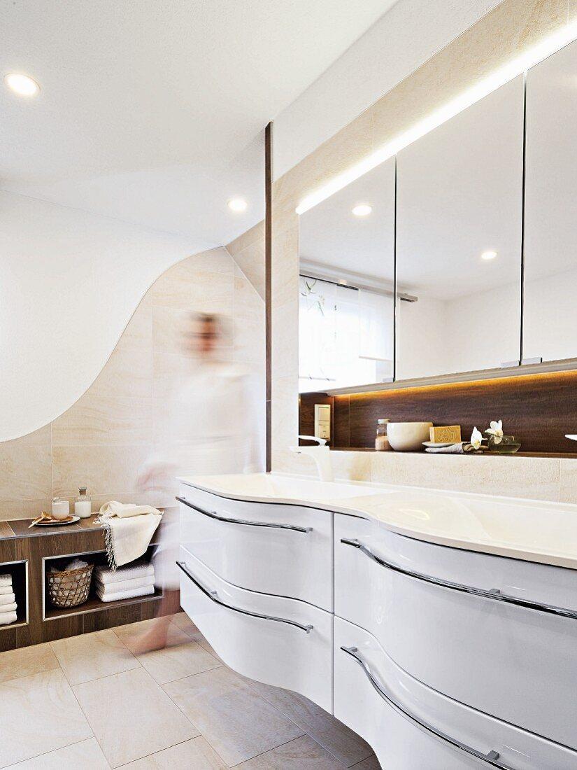 A curved white sink unit in an elegant designer bathroom