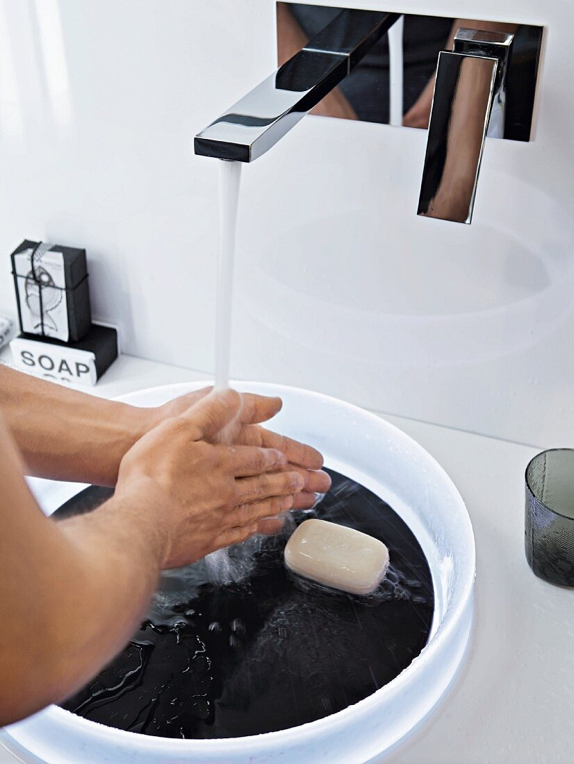 Washing over a white plastic bowl with a black base in a slate design and a wall-mounted designer tap