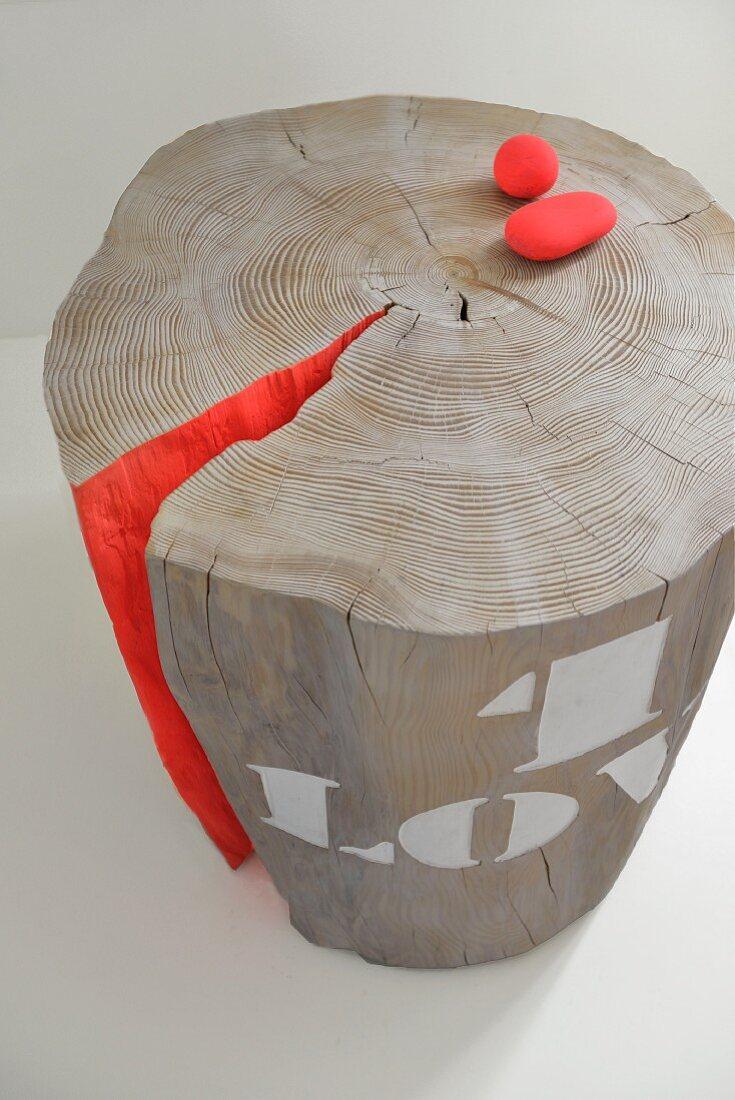 Red-painted pebbled on tree-stump stool