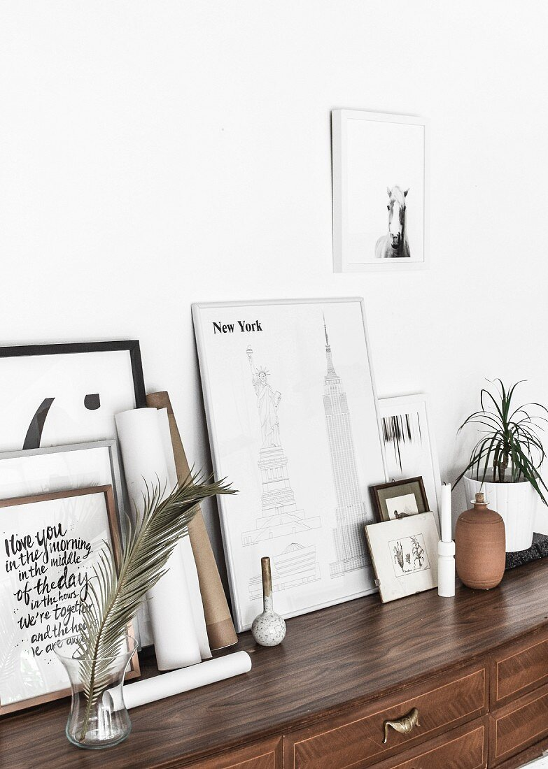Pictures and framed graphic artworks on top of old chest of drawers