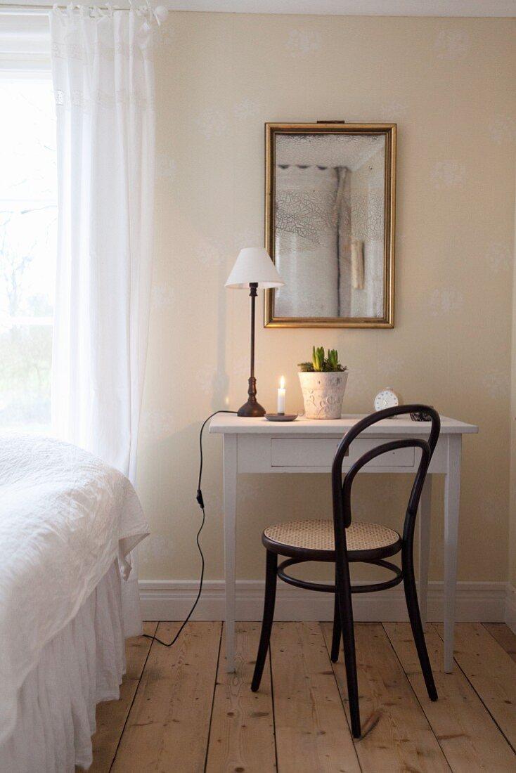 Black bistro chair at white desk below mirror