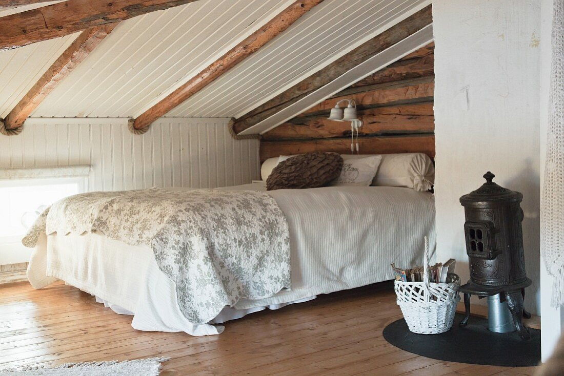 Wood-beaming sloping ceiling and small stove in rustic attic bedroom