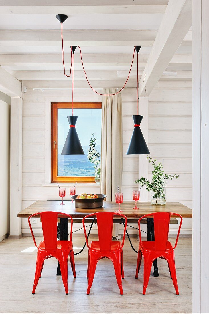 Red metal chairs around wooden table in … – Buy image – 9 ...