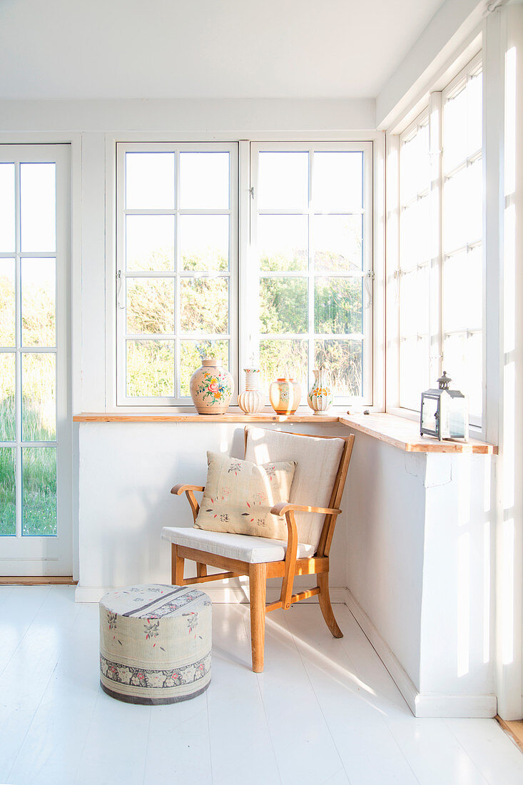 Wooden armchair and footstool in bright conservatory
