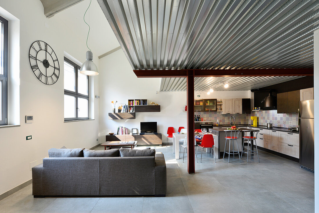 Grey couch, kitchen and dining area with red chairs in living area of industrial loft apartment