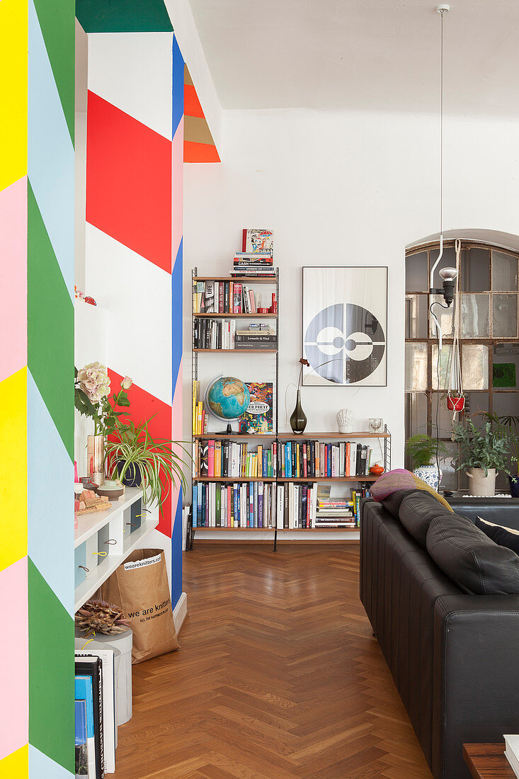 Colourful partition with wide stripes, black leather couch and book shelves