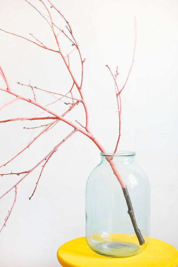 Rosafarben bemalter Zweig im Einmachglas auf gelbem Hocker
