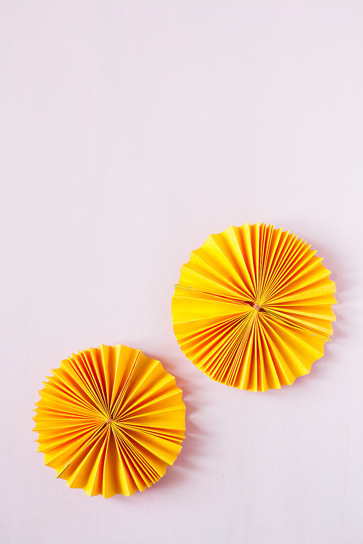 Two sunny yellow paper rosettes on pink surface