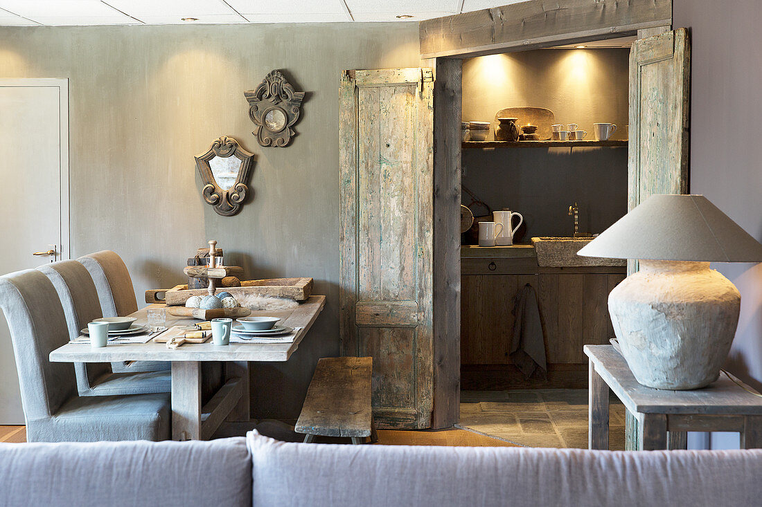 Set table in rustic dining room with double doors leading into kitchen