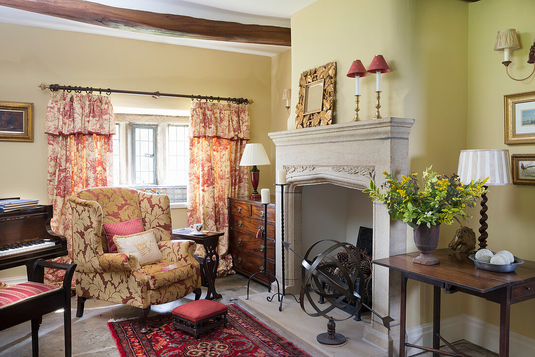 Polstersessel vor Kamin und Klavier in ländlichem Wohnzimmer