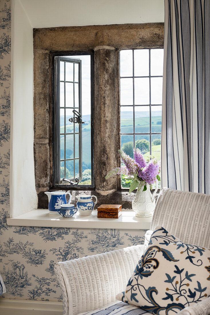 Rattansessel mit Kissen vor rustikalem Fenster und Toile De Jouy Tapete