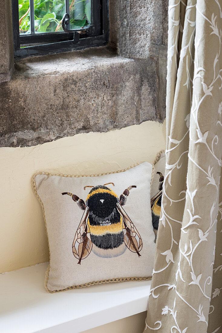 Kissen mit Bienenmotiv auf Ablage unter rustikalem Fenster