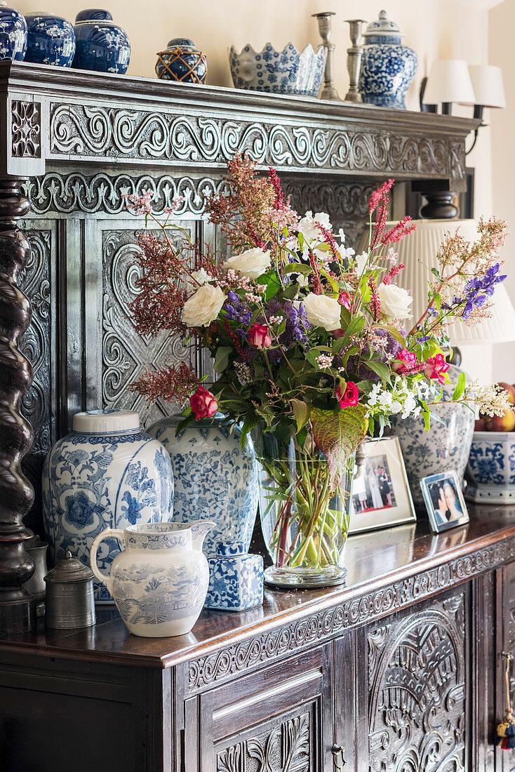 Üppiger Blumenstrauß und Vasen auf antiker Anrichte mit Holzschnitzerei
