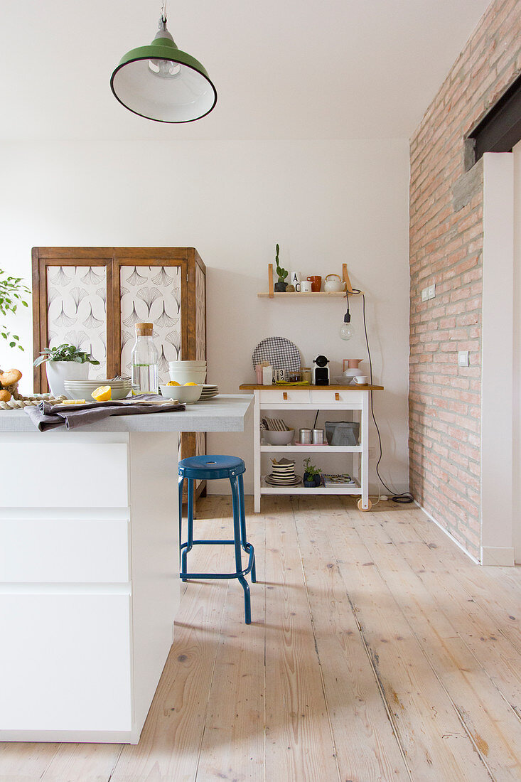 White kitchen island and blue barstool in open-plan kitchen with wooden floorboards and exposed brick wall