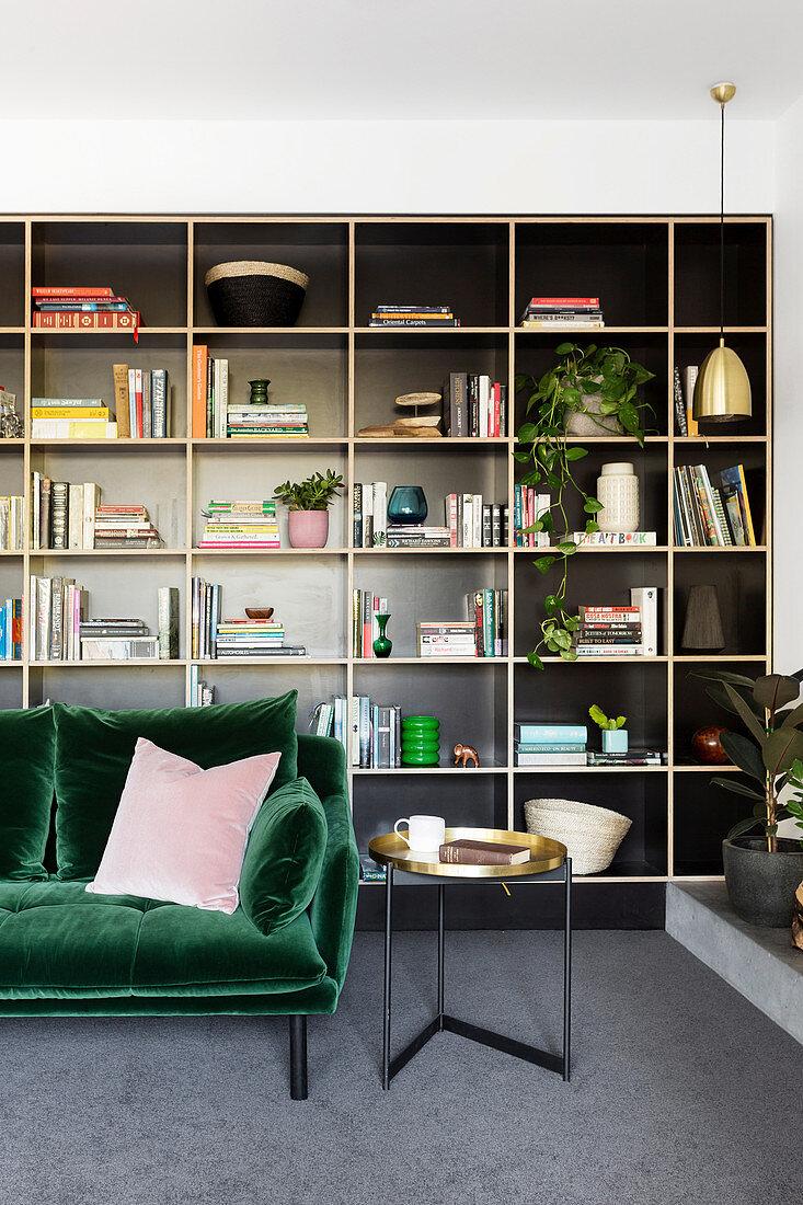 Dark green velvet sofa against a black shelf