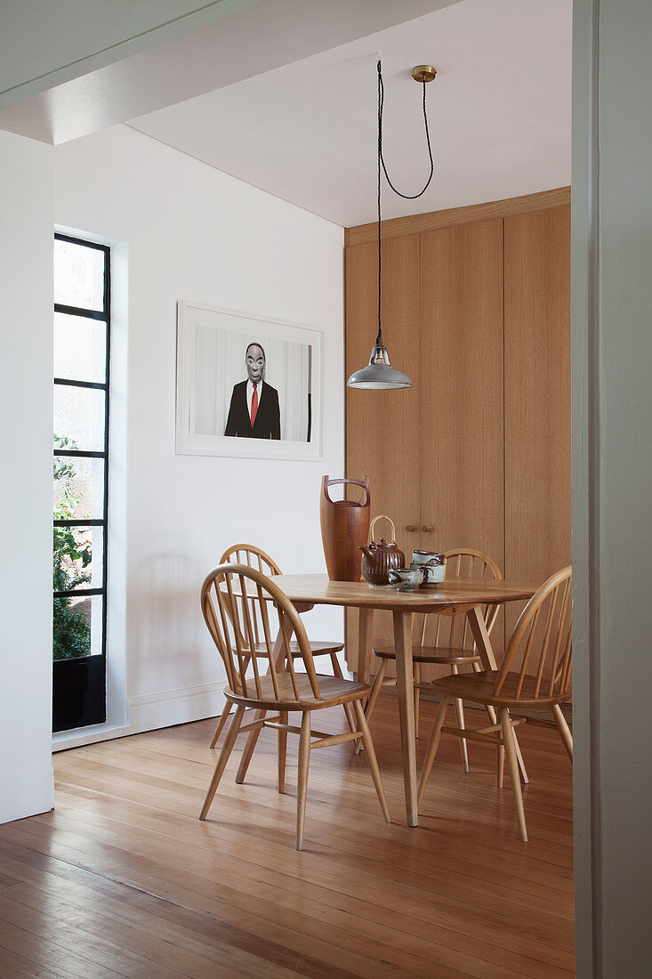 Spoke-back chairs around pale wooden kitchen table next to fitted cupboards