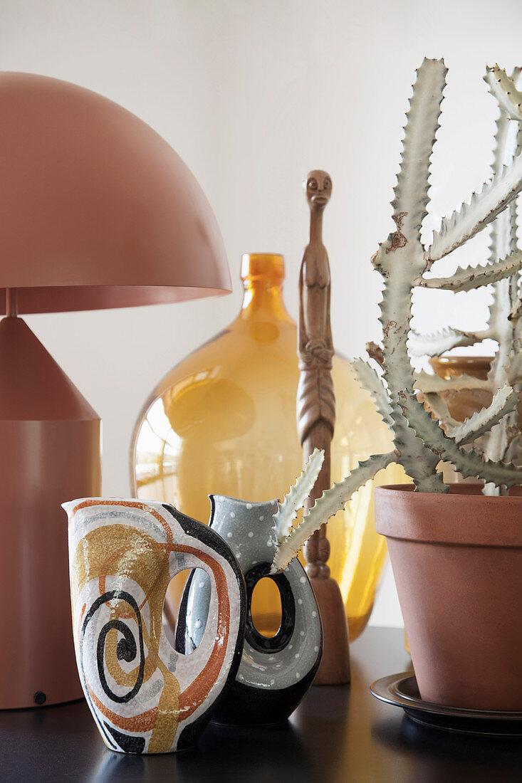 Mid-century modern arrangement of vases, designer lamp and cactus