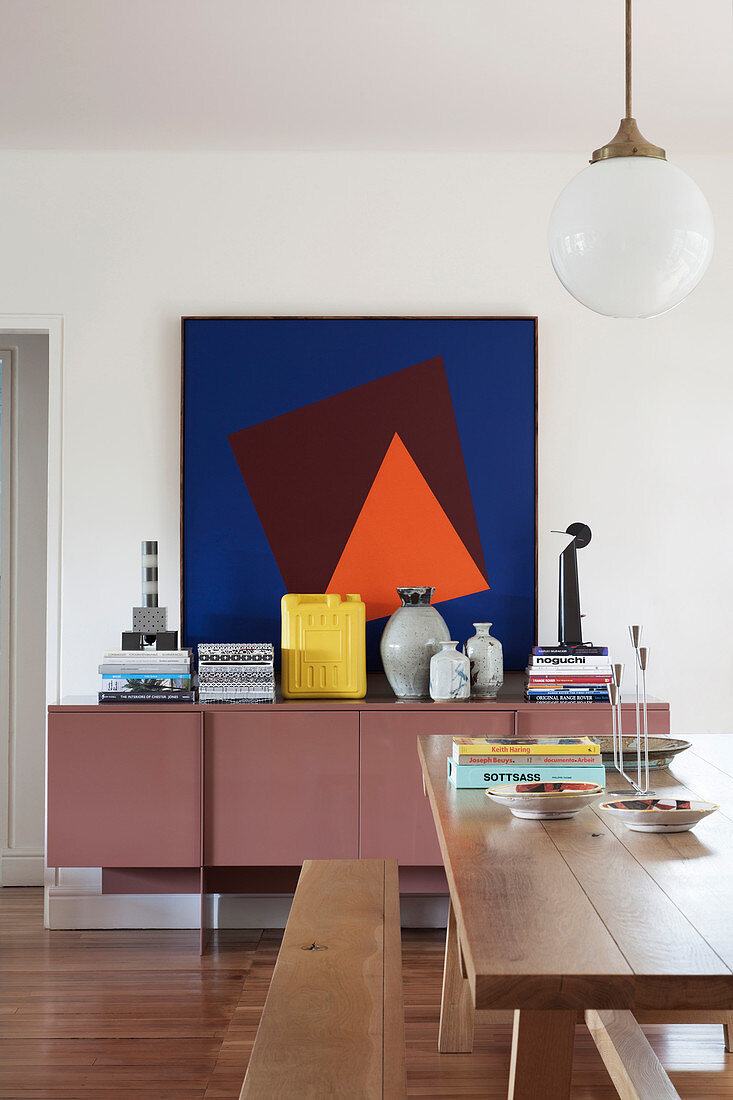Modern graphic painting above mauve sideboard in dining room