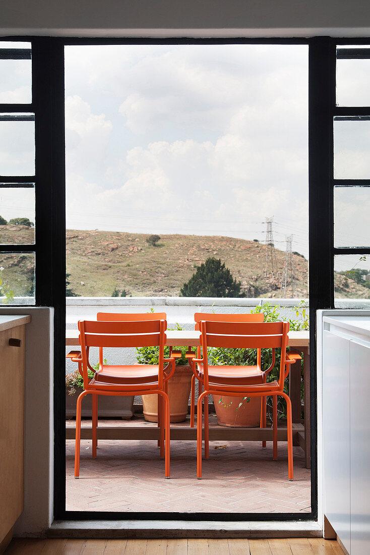 Orange chairs around table on balcony below cloudy sky